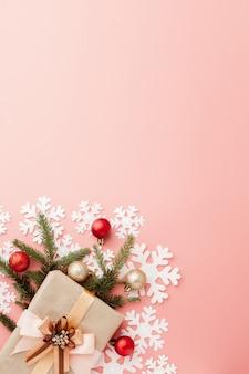 ピンクの背景にリボンで包まれたささやかな贈り物のショットを閉じます。クリスマスの背景。最小限のコンセプト。平干し。上面図