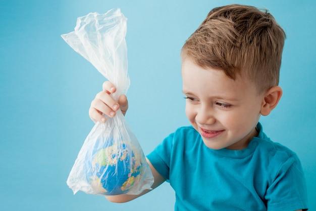 Маленький мальчик с глобусом в пакете на синем фоне