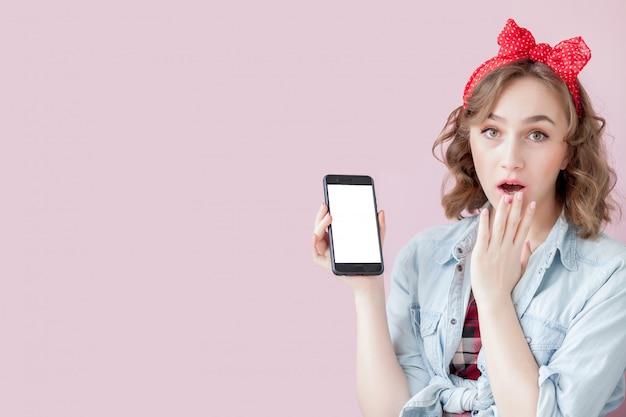 ピンのメイクアップと携帯電話で髪型と美しい若い女性
