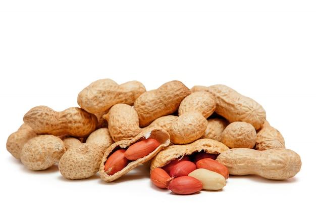 白で隔離シェルで豆の大きな皮をむいたピーナッツのクローズアップ