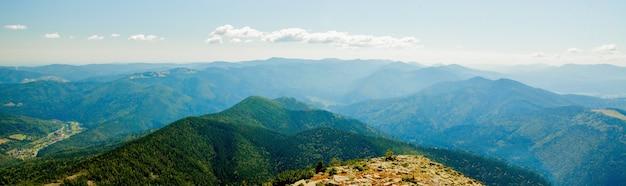 森林と曇り空に覆われた山頂の美しい山の風景。