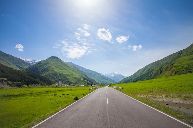 Горная пустая дорога, зеленые холмы, голубое солнечное небо