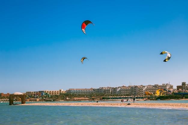 Красочные воздушные змеи, парящие над берегом красного моря.