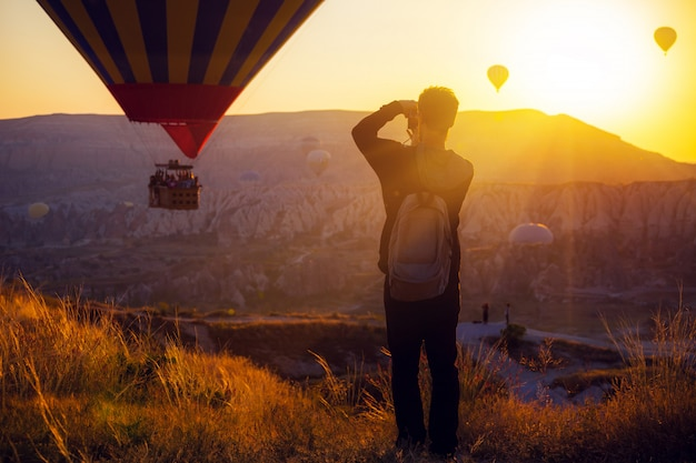 熱気球の写真を撮る男