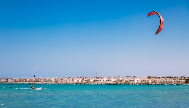 Кайтбордер скользит по поверхности красного моря.