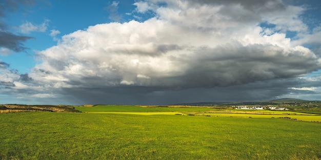 緑の野原の上の雨の空。北アイルランド。
