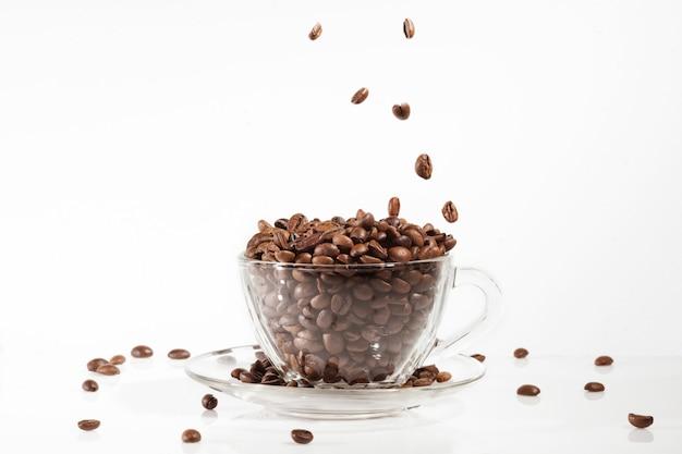 Кофейная чашка с кофейными зернами на белом