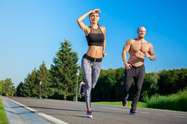 Мужчина и женщина бегут в парке