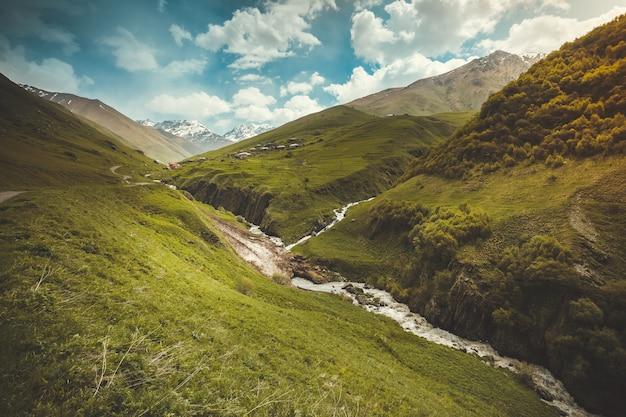 川と山の雪のピークのある夏の風景