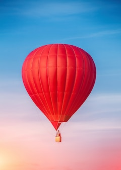 Краснокалильный воздушный шар в голубом небе. концепция путешествия