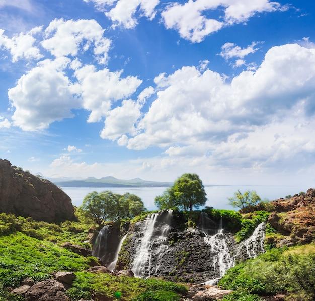 青い曇り空と山の滝