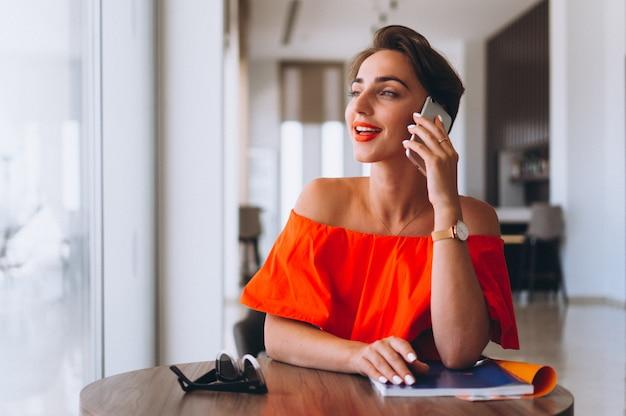 雑誌と電話で美しい女性