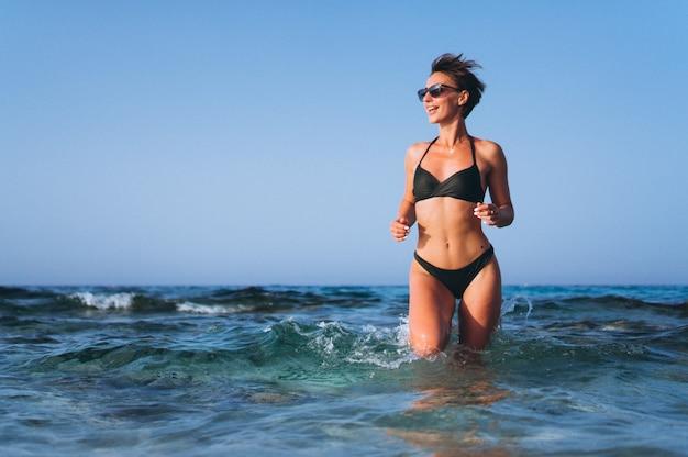 美しい女性が海から走っている