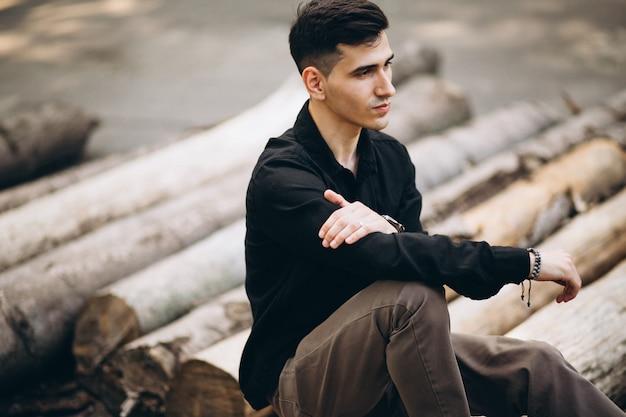 公園のログに座っている若いハンサムな男