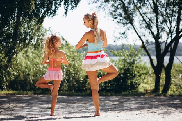 ヨガを実践しているビーチの母と娘