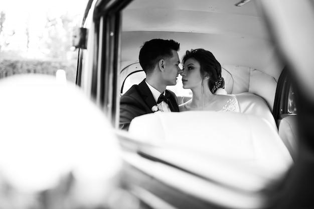 レトロカーで結婚式のカップルの写真撮影