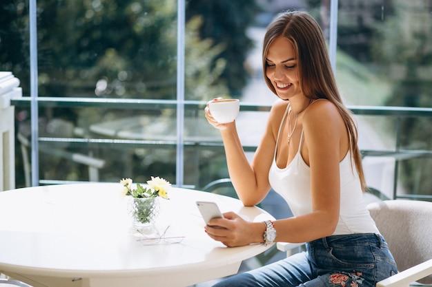 コーヒーを飲んで電話で話すカフェの女性