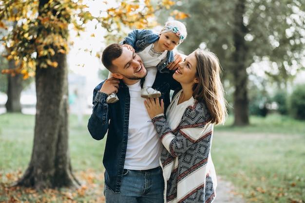 秋の公園に小さな娘がいる若い家族