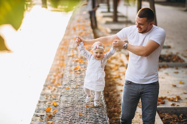 公園で歩いている娘と父親