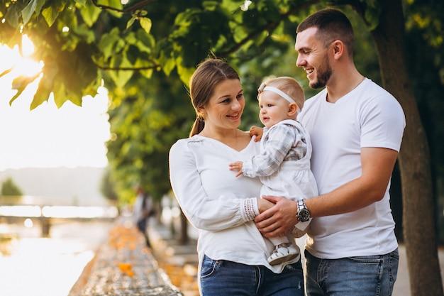 Молодая семья с маленькой дочкой в осеннем парке