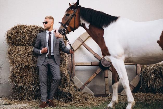 馬の牧場でのスーツのハンサムな男