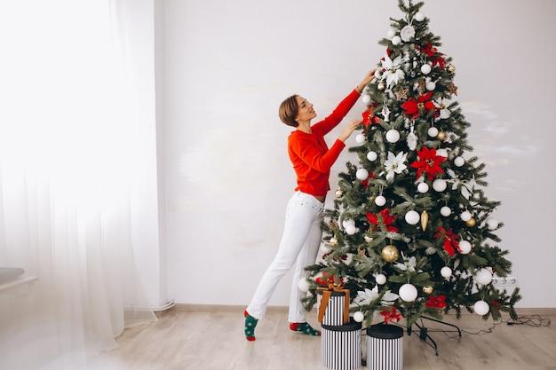 Женщина, украшающая елку