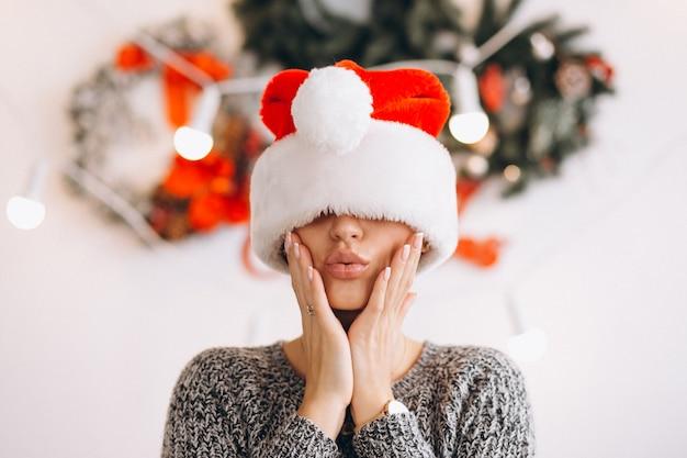 クリスマスのサンタの帽子の女性の肖像