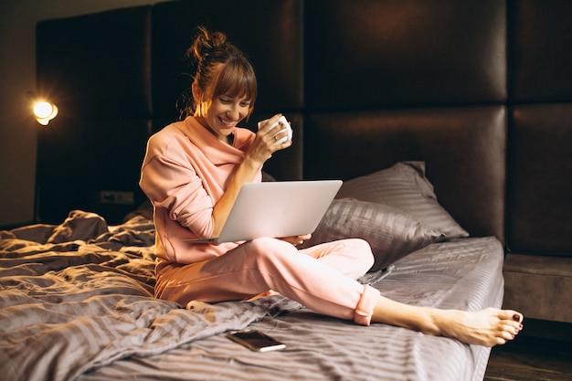 ベッドでラップトップで働くピガマの女