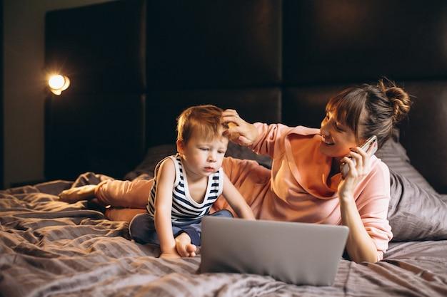 ベッドでコンピュータで働く息子と母