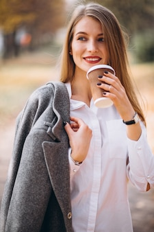 屋外でコーヒーを飲む若いビジネスの女性