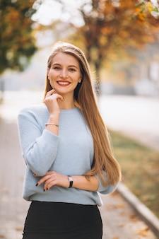 秋の公園で青いセーターの若い女性