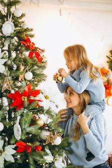 Мать с дочерью, украшающей елку