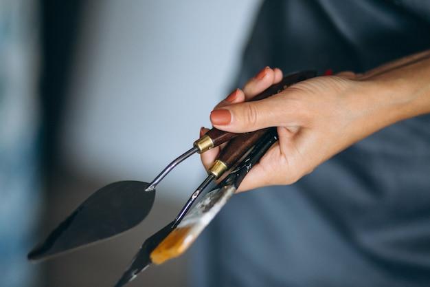 女性の手は、パレットナイフとアートブラシを保持して閉じる