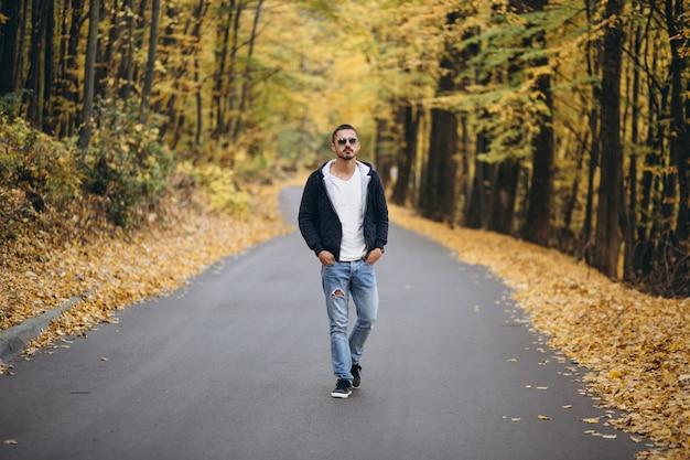 秋の公園で道路に立っている若い男