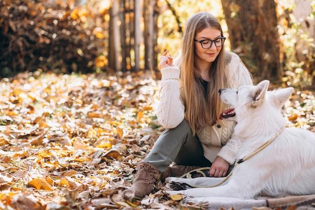 毛布に座っている公園で彼女の犬と女