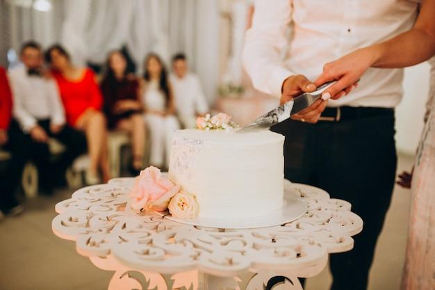 ウェディングケーキをカットするウェディングカップル