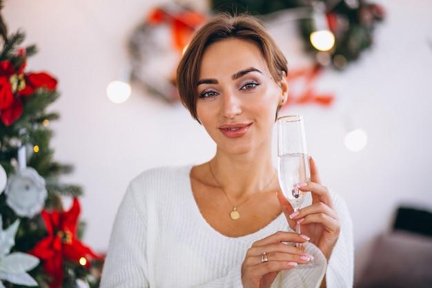 クリスマスツリーでシャンパンを飲む女性