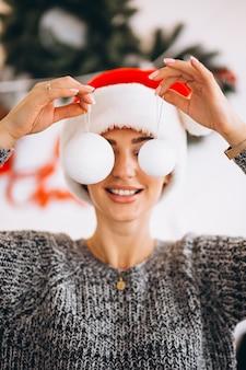 彼女の目の前にクリスマスツリーのおもちゃを保持しているクリスマスの女性