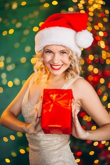 Молодая женщина в платье с рождественские подарки на елку