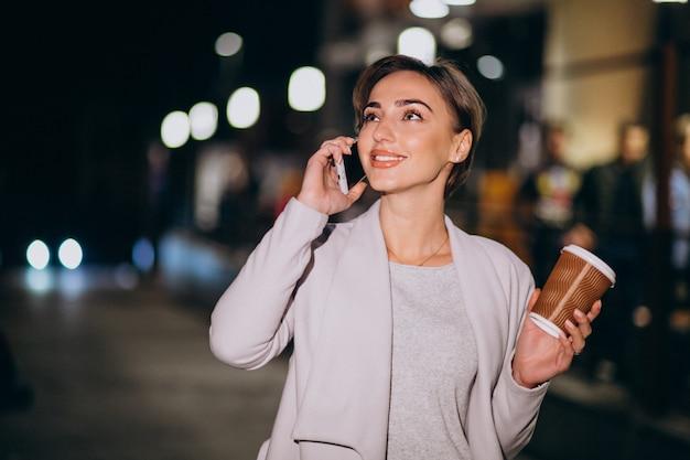 女性が電話で話していると夜に路上で外のコーヒーを飲む