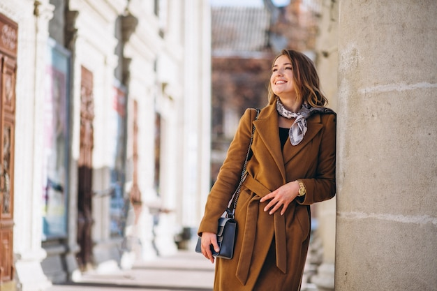 Деловая женщина счастлива в пальто на улице