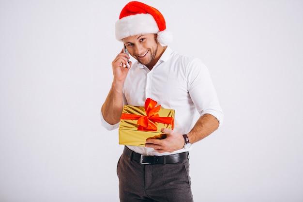 白い背景で隔離のサンタ帽子で電話で話しているビジネスマン