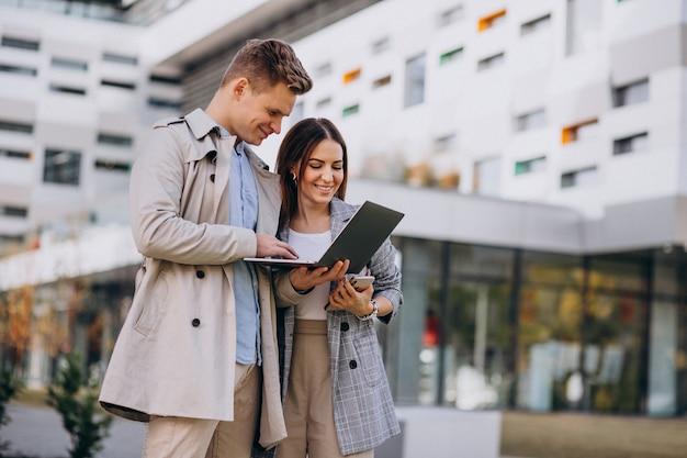 若いカップルが一緒に外に立っているとコンピューターを使用して