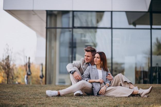 建物のそばの芝生の上に座っている若いカップル