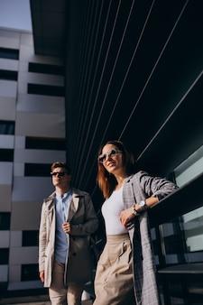建物のそばに立っている若いカップル