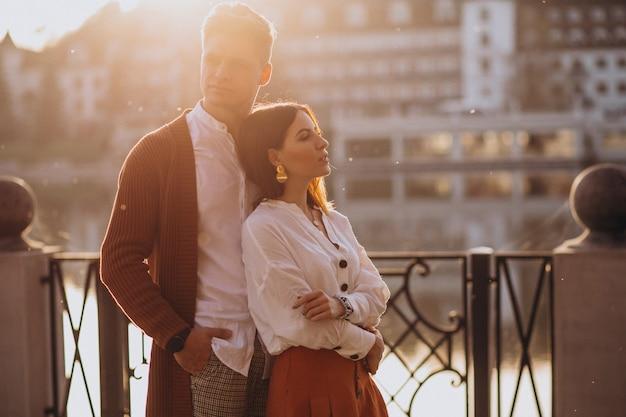 Пара обнимается на улице у реки