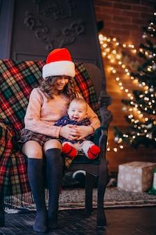 クリスマスツリーで椅子に座っている弟と妹