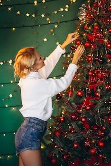 若い女性のクリスマスツリーを飾ること