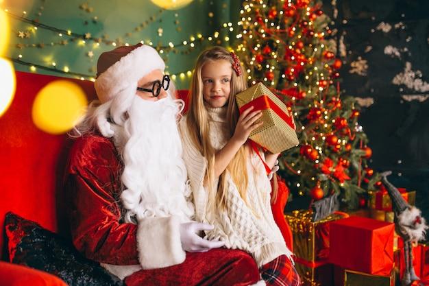 サンタとクリスマスプレゼントに座っている小さな女の子