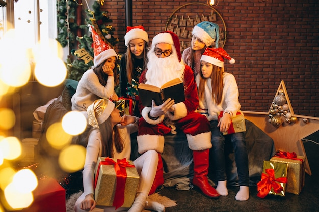 Санта-клаус читает книгу группе детей